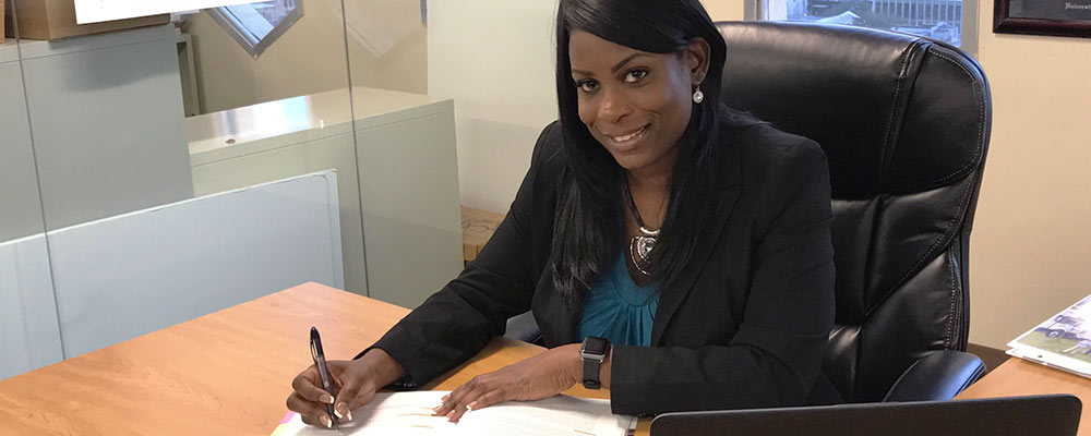Akiesha, Manager of Project Accounting, working in her office