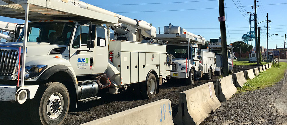 OUC utility trucks line up for shipment from Jacksonville to Puerto Rico