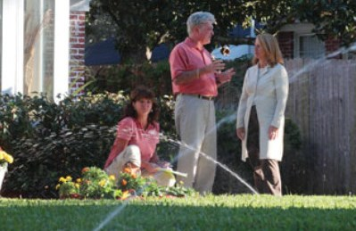 Family Standing Outside While Watering the Lawn