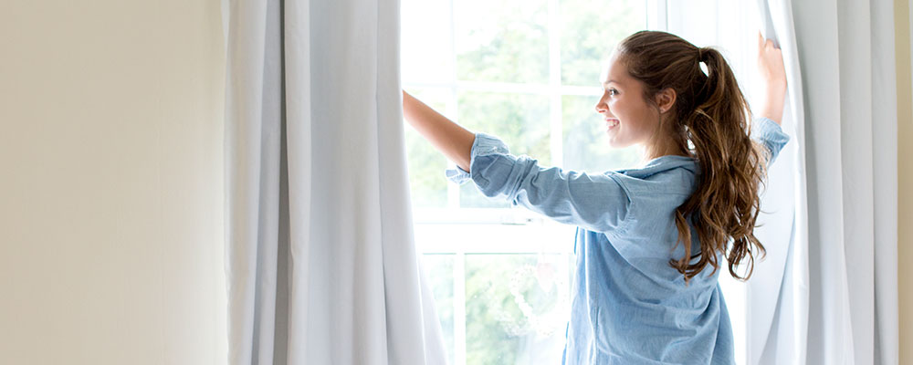 Woman opening curtains